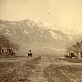 historic black and white photo of early settlement in Colorado Springs; a dirt road with buildings to either side and Pikes Peak in the background