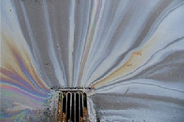 Oil spilling into a storm drain