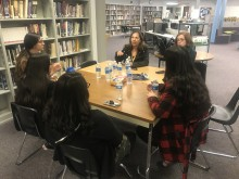 Counciwoman Yolanda Avila sits with students around a table in the library