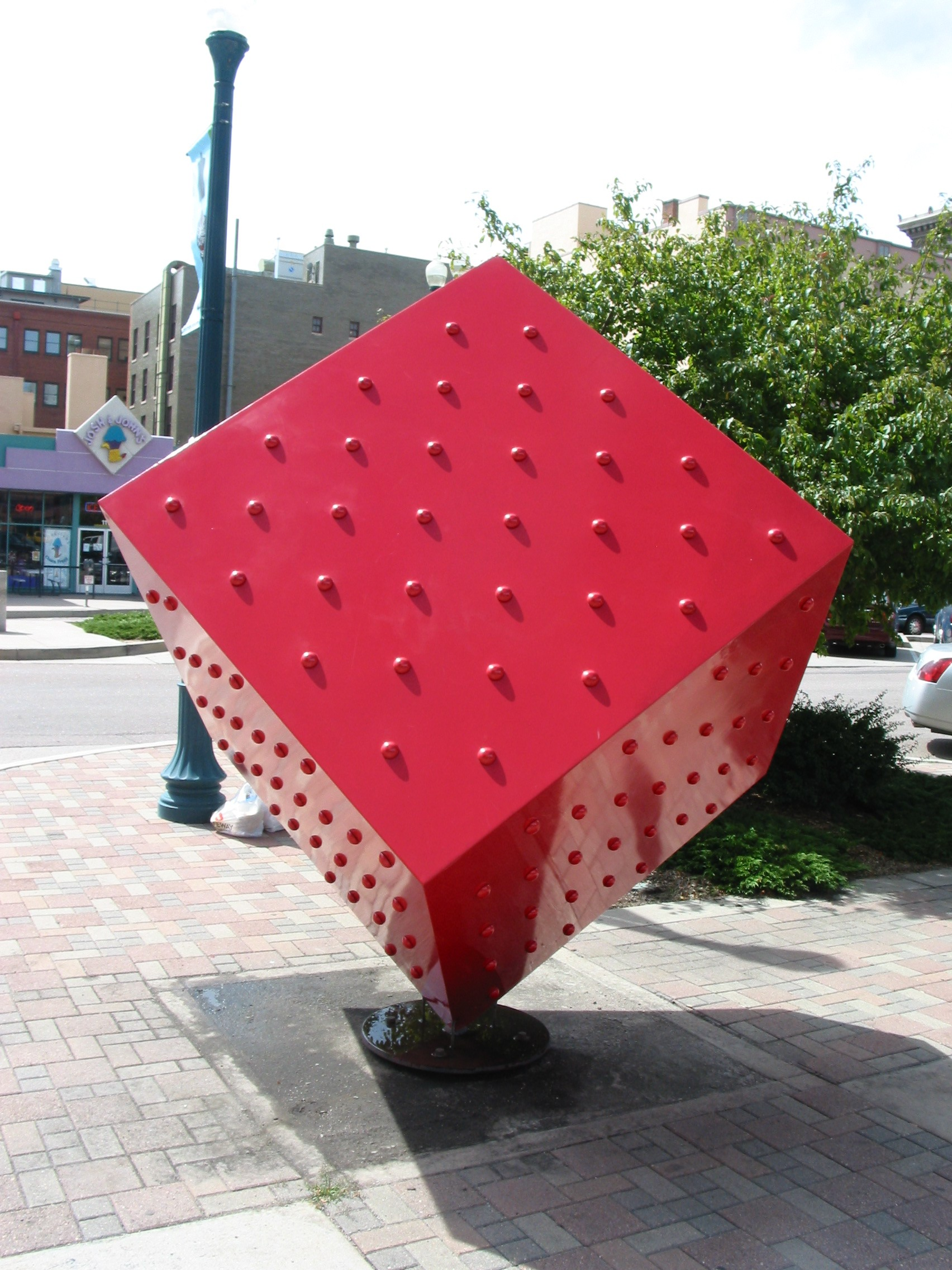 large red cube balancing on one corner