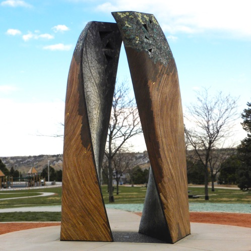 sculpture made of two large wooden columns standing side-by-side and curve slightly toward one another