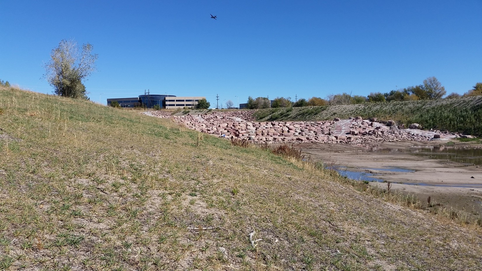 After - Image of grassy creek bank and stone spillway