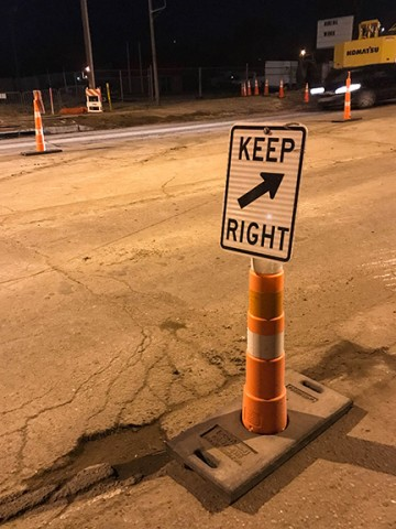 orange cone in construction zone at night with a sign that reads keep right