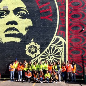 student ambassadors pose in front of a mural