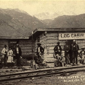 Historic black and white photo of a log cabin at the base of Pikes Peak with a group of early settlers to the region out front