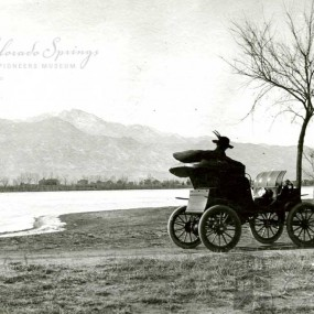 historic black and white photo of a buggy in front of Prospect Lake with Pikes peak in the background