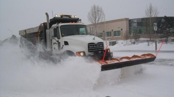photo of a snowplow plowing the street