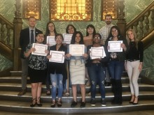 Students show off certificates as they pose for the camera on the steps of City Hall's atrium.