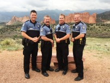 Four male police officers who are members of the homeless outreach team pose for a photo in front of Garden of the Gods