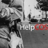 """hands of a homeless person sitting on a bench. text says """"help cos"""""""