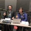 Jen and Ted give thumbs up from the audio booth. Gray sound proof materials on the way behind them, studio microphones and sound board in front.